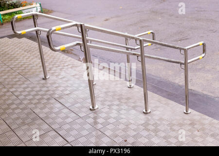 Stainless steel handrails are installed on the walls and steps.steel handrail.assistance for people with limited mobility, for the elderly.Copy space.stairway enclosure with metallic stair railing outside building - Stock Photo