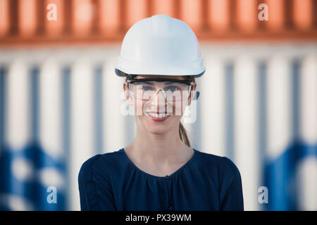woman logistics engineer is standing in front of containers
