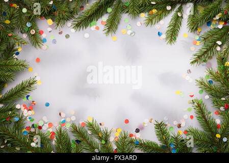 Christmas decorative background for design. Frame made of fir branches and confetti. Flat lay, top view, copy space for text - Stock Photo