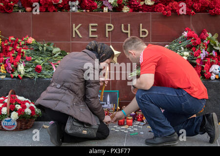 Moscow, Russia. 17th October, 2018. A woman and man lays candels at the WWII Hero Cities Memorial to the city of Kerch in downtown Moscow on October 18, 2018, a day after a 18-year-old student opened fire on his fellow students, leaving at least 21 people dead and dozens injured in a Crimean technical college in Kerch, Crimea. Credit: Victor Vytolskiy/Alamy Live News - Stock Photo
