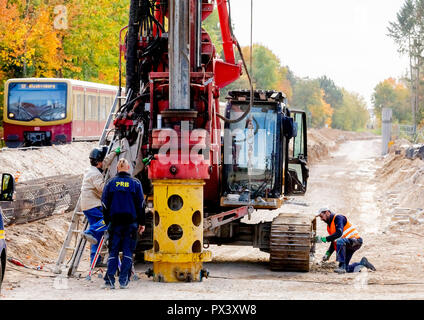 Berlin, Germany. 19th Oct, 2018. Construction workers are waiting for a drill on the future route of the Dresden Railway in the section between the Lichtenrade S-Bahn station and the Berlin-Brandenburg border, while an S-Bahn passes by. Deutsche Bahn is pushing ahead with the expansion of the line in the direction of Dresden and the BER in the south of Berlin. (to 'Railway is driving the construction of the Dresden railway' from 20.10.2018) Credit: Christoph Soeder/dpa/Alamy Live News - Stock Photo