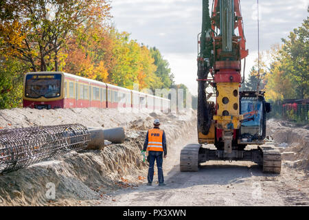 Berlin, Germany. 19th Oct, 2018. A construction worker is standing on the future route of the Dresdner Bahn in the section between the S-Bahn station Lichtenrade and the border Berlin-Brandenburg between a drill and a passing S-Bahn. Deutsche Bahn is pushing ahead with the expansion of the line. (to 'Railway is driving the construction of the Dresden railway' from 20.10.2018) Credit: Christoph Soeder/dpa/Alamy Live News - Stock Photo