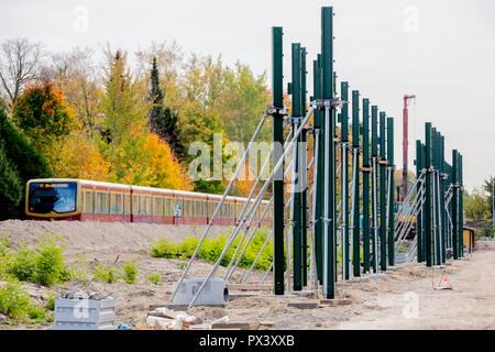 Berlin, Germany. 19th Oct, 2018. Posts for noise barriers are located in the section between the Lichtenrade S-Bahn station and the Berlin-Brandenburg border along the future route of the Dresden Railway, while an S-Bahn passes by. (to 'Railway is driving the construction of the Dresden railway' from 20.10.2018) Credit: Christoph Soeder/dpa/Alamy Live News - Stock Photo