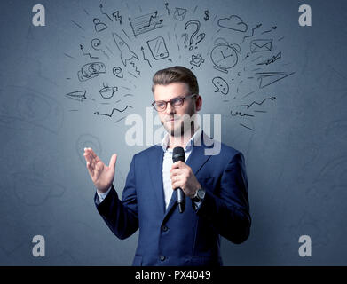 Businessman speaking into microphone with mixed doodles over his head - Stock Photo