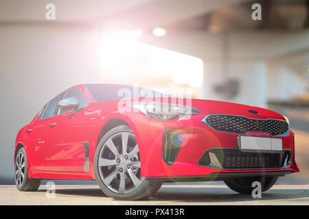 A red car on a background of city environment. Stylish, modern, bright image of the car for design solutions. - Stock Photo