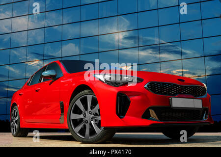 Red car against the background of the evening sky. Stylish, modern, bright image of the car for design solutions. - Stock Photo