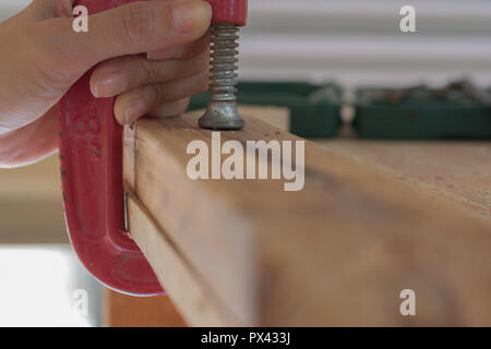 Close Up of Woman Using a C Clamp - Stock Photo