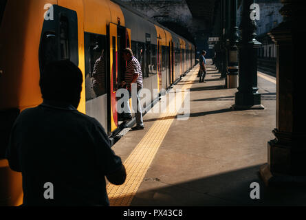 People enter into train in trainstation on summer day, Portugal - Stock Photo