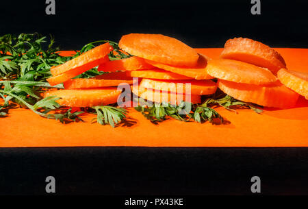 Freshly and sliced carrots on green leaves , dark and orange background , studio shot , front view , - Stock Photo