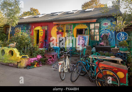 COPENHAGEN, DENMARK - October 2018: Small, colorful art shop in Freetown Christiania, a self-proclaimed autonomous neighbourhood in Copenhagen. Painting of Kim Larsen. Bicycles parked outside. - Stock Photo
