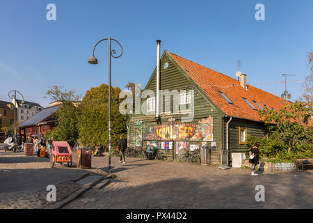 COPENHAGEN, DENMARK - October 2018: Street with buildings and people in Freetown Christiania, a self-proclaimed autonomous neighbourhood in Copenhagen. - Stock Photo