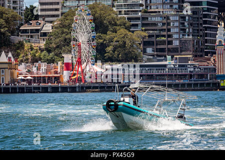 Small speed boat travelling at speed in front of Luna Park Ferris Wheel in Sydney Harbour, Sydney, Australia on 7 January 2015 - Stock Photo