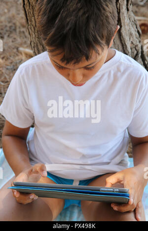 11-year-old boy using a digital tablet in Salento, Italy. - Stock Photo