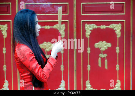 Vietnamese woman in red traditional long dress Ao Dai praying with incense sticks.  Ho Chi Minh City. Vietnam. - Stock Photo
