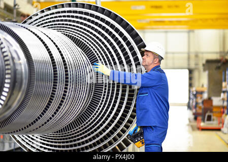 workers manufacturing steam turbines in an industrial factory - Stock Photo
