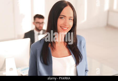 Business cheerful woman is standing in the foreground - Stock Photo