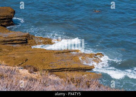Ocean waves crashing onto rocky shoreline. - Stock Photo