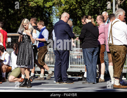 Oktoberfest party goers waiting for the train at Riem Station on the U-Bahn in Munich. Blond German woman holding a mobile phone. - Stock Photo