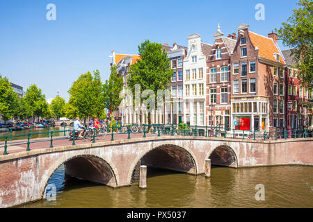 Amsterdam People on bicycles cross the bridge over the Keizergracht canal at its junction with Leilesgracht Amsterdam Netherlands Holland EU Europe - Stock Photo