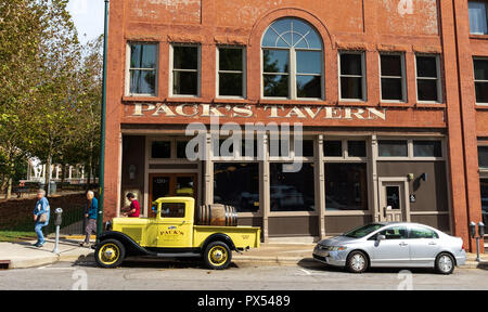 ASHEVILLE, NC, USA-10/17/18: Three people walk past Pack's Tavern on Spruce Street, with vintage Pack's Tavern pickup setting in front. - Stock Photo