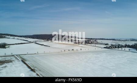 Drone shot aerial Snowy white winter farmland landscape in Elm mountain range Germany - Stock Photo