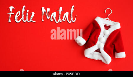 Feliz Natal (in Portuguese: Merry Christmas) text and Santa Claus (Saint Nicholas) coat suit costume with white clothing cuffs isolated on vivid red b - Stock Photo
