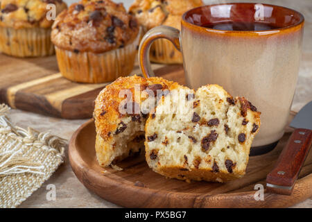 Closeup of a chocolate chip muffin cut in half and a cup of coffee on a wooden plate with muffins in background - Stock Photo