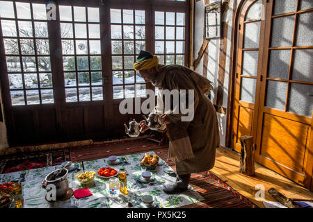 Sufi sheikh serving breakfast at the 'Douce France' sufi house in Romilly, France. - Stock Photo