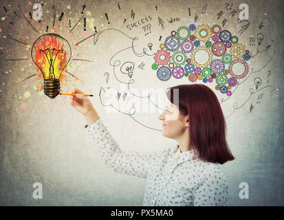 Young woman with colorful gear brain above head, positive emotion, drawing a genius idea as arrows and curves going to a color splash light bulb. Conc - Stock Photo