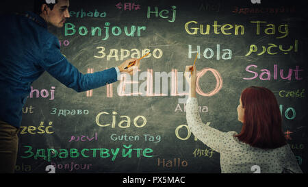 Man and woman together drawing word hello in different languages and colors on blackboard. Opportunity for learning many languages for students. Busin - Stock Photo