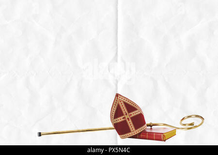 Mitre or miter book, gifts and staff of saint nicholas. on folded paper background - Stock Photo