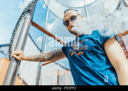 Portrait of young vaping man with dreadlocks at art object background. Vapor concept. Vaping e-Cigarette - Stock Photo