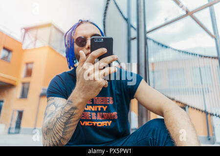 Young attractive man with blue dreadlocks looking at mobile phone screen. - Stock Photo