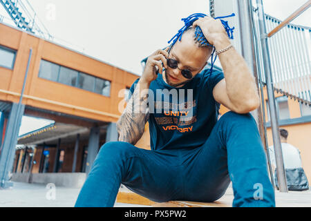 Young attractive man with blue dreadlocks talking by mobile phone and touching his hair. - Stock Photo