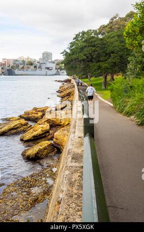 Man jogging on path along Woolloomooloo Bay and Royall Botanic Garden Sydney NSW Australia. - Stock Photo
