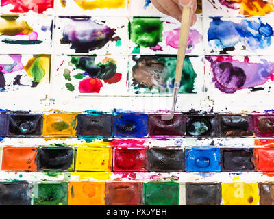 top view of paintbrush mixes color in set of used watercolor paints with pallet - Stock Photo
