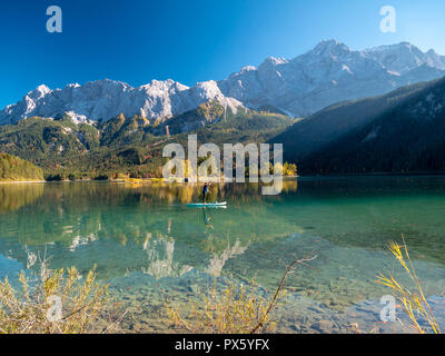 Image of stand up paddling on a beautiful mountain lake in autumn