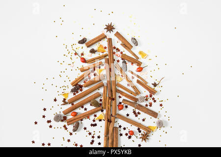 Christmas tree made of cinnamon sticks, cones, oranges, shiny stars and presents. White background, top view, flat lay - Stock Photo