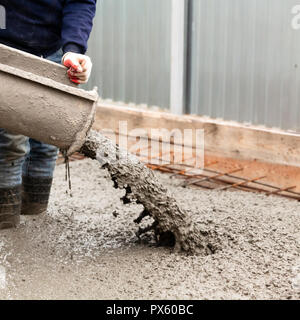 Closeup shot of concrete casting on reinforcing metal bars of floor in industrial construction site - Stock Photo