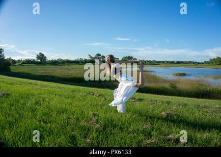 blonde woman spiritual doing yoga king dance, standing pulling bow, Natarajasana Dandayamana Dhanurasana pose in a field in nature - Stock Photo
