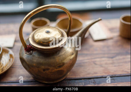 Copper teapot close up on a wooden table - Stock Photo