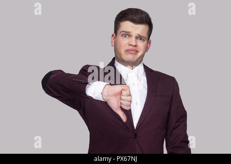 Portrait of handsome confused young man in violet suit and white shirt, standing, looking at camera with thumbs down and unsatisfied face. indoor stud - Stock Photo