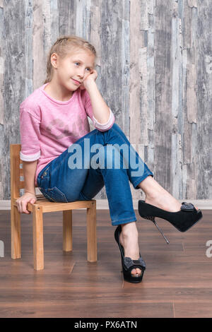 Young beautiful girl in her mother shoes sits on a small wooden chair and dreams of leaning on her arm - Stock Photo