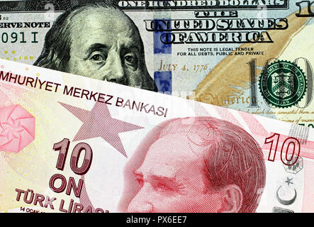 A close up image of a blue American one hundred dollar bill with a ten Turkish lira bill - Stock Photo