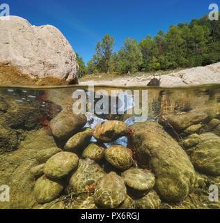 Rocky river, split view half over and under water, La Muga, Alt Emporda, Catalonia, Spain - Stock Photo