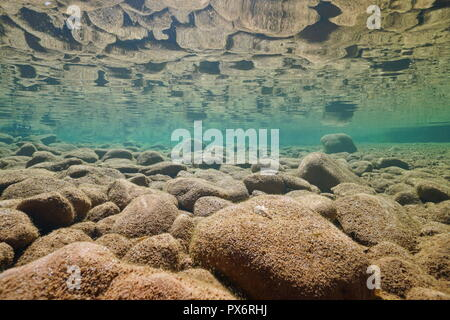 Underwater rocky riverbed in shallow water reflected in the calm water surface, La Muga river, Alt Emporda, Catalonia, Spain - Stock Photo