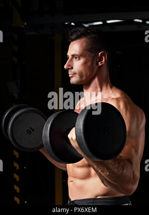 Handsome strong brutal man doing the exercises with dumbbells on dark sport club background. Training in light gym in art shadow. Profile view - Stock Photo
