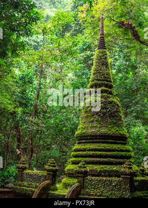 Green moss covered the old beautiful pagoda at Phlio waterfall national park, Chanthaburi in Thailand - Stock Photo