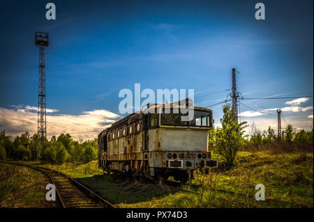 Old diesel locomotive in train cemetery in the summer with green grass and trees in the background and great cloudy sky - Stock Photo
