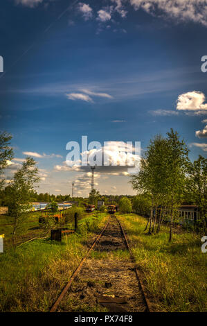 Old locomotives in train cemetery in the summer with green grass and trees in the background and great cloudy sky - Stock Photo